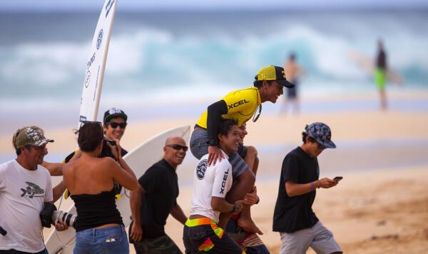 Josh Moniz gets a winner's welcome up the beach after winning the Pipeline Pro Junior.
