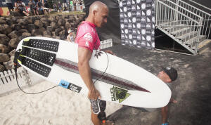 Kelly Slater exits the Quiksilver Pro Gold Coast with a Tomo surfboard.